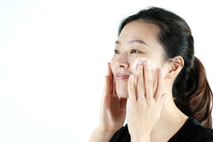 Cute asian girl applying cream lotion on face, isolated on white background Royalty Free Stock Images