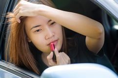 Asian girl applying makeup while in the car Stock Photos
