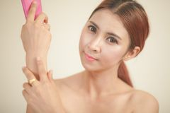 Asian girl applying moisturizer Royalty Free Stock Photo