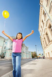 Asian girl with arms up holds flying balloon Stock Photo
