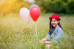 Asian girl with balloons plays in a field Royalty Free Stock Image