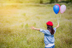 Asian girl with balloons plays in a field Royalty Free Stock Images