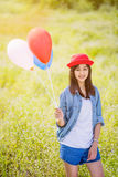 Asian girl with balloons plays in a field Stock Images