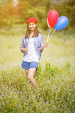 Asian girl with balloons plays in a field Royalty Free Stock Photos