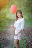 Asian girl with balloons plays in a field Stock Photos