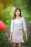 Asian girl with balloons plays in a field Royalty Free Stock Photography