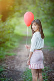 Asian girl with balloons plays in a field Stock Photography