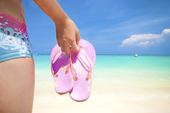 Asian girl on a beach holding slipper Stock Image