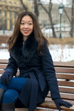 Asian girl. Beautiful Asian girl in winter coat on the bench Stock Images