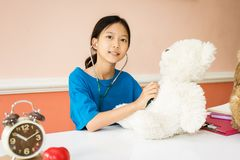 Asian girl being played as a doctor with heart disease. To teddy bears Royalty Free Stock Photo