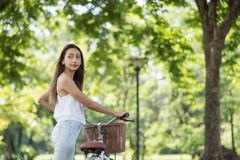 Asian girl with bicycle in park. Asian Beautiful happy  woman look at summer garden while  wheel a bicycle by hands at park with foliage bokeh background. People Stock Photo