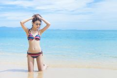 Beautiful Asian woman in bikini relaxing on beautiful beach. Asian girl in bikini relaxing on the beach royalty free stock photography
