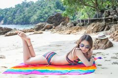 Asian Girl in bikini relaxing on the beach. Asian Girl in bikini and straw hat on tropical beach royalty free stock photography