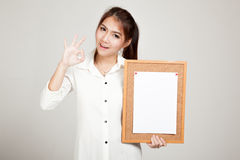 Asian girl with blank paper pin on cork board stock photos