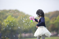 Asian girl blowing soap bubble in park Royalty Free Stock Images