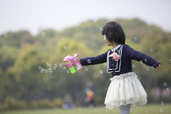 Asian girl blowing soap bubble in park Stock Photos