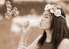 Asian girl blowing soap bubbles, Outdoor portrait. With Sepia toning Royalty Free Stock Image