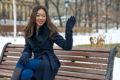 Asian girl. In blue coat on the bench raised in greeting hand Stock Photography