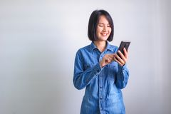 Asian girl with blue shirt left hand holding phone stock image