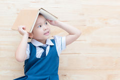 Asian girl with book on head thinking on wood Stock Photos
