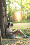 Asian girl with book and headphone siting Royalty Free Stock Photo