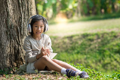 Asian girl with book and headphone siting Royalty Free Stock Photos