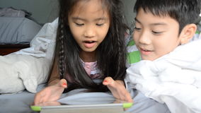Asian girl and boy play on tablet on the bed stock video footage