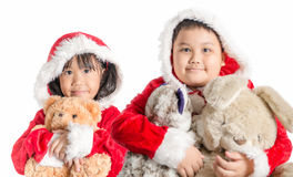 Asian girl and boy in santa costume hugging bear doll on christmas royalty free stock photos