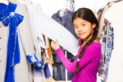 Asian girl with braid between clothes on  hangers Stock Photography