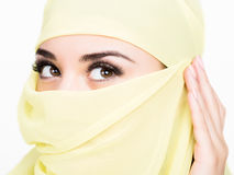 Asian girl with brown eyes posing in a yellow scarf, muslimah model in hijab isolated in white background Stock Photography