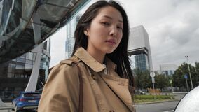 Asian girl in brown trench poses in the city center