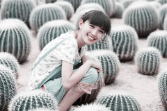 Asian girl in cactus field. Charming Asian girl smiling in ball cactus field Stock Image