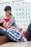 Asian girl caressing her boyfriend Royalty Free Stock Photos