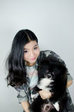 Asian girl with black pommeranian puppy Royalty Free Stock Photo