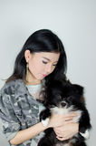 Asian girl with black pommeranian puppy Stock Photo
