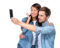 Asian girl and caucasian boy take selfie Stock Photo