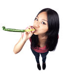 An Asian girl celebrating with a noise maker. A wide angle full body shot of an Asian girl holding a noise maker and celebrating Stock Photo