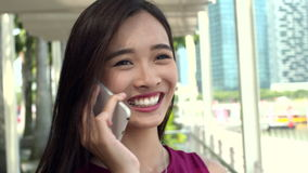 Asian girl chatting over her phone outdoor stock footage