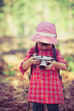 Asian girl checking photos in digital camera. Vintage picture  Stock Photo