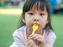 Asian girl child eating a dessert , spoon in her mouth Royalty Free Stock Photos