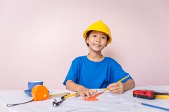 Asian girl child playing as an engineer the building layout. And helmet are smiling and happy on weekends Royalty Free Stock Images