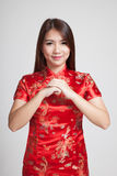 Asian girl in chinese cheongsam dress with gesture of congratulation royalty free stock photography