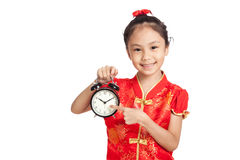 Asian girl in chinese cheongsam dress point to a clock Stock Image