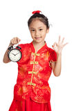 Asian girl in chinese cheongsam dress show OK sign with a clock Stock Image