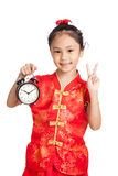 Asian girl in chinese cheongsam dress show victory sign with a c Royalty Free Stock Images