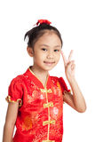 Asian girl in chinese cheongsam dress show victory sign Stock Image
