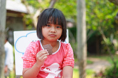 Asian girl with chocolate. In her hand Royalty Free Stock Photography