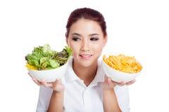 Asian girl choose salad over crisps. Isolated on white background royalty free stock image
