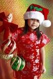 Asian girl with christmas balls royalty free stock photography
