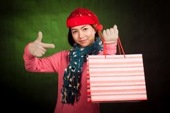 Asian girl with christmas hat point to shopping bag Royalty Free Stock Photography